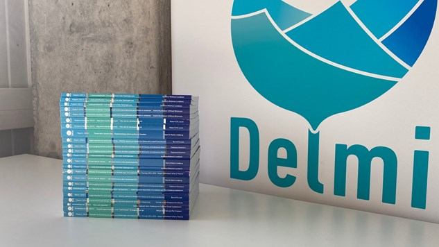 Several Delmi-reports on a table in front of a roll-up with Delmis logo on.